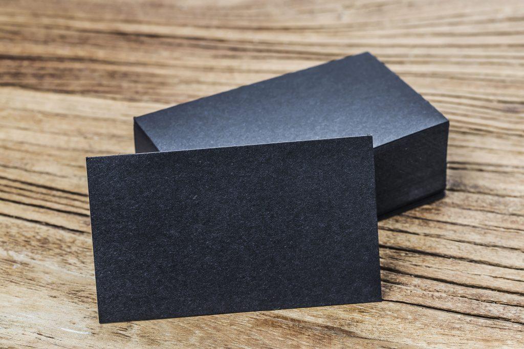 Schwarze Visitenkarten auf Holzhintergrund